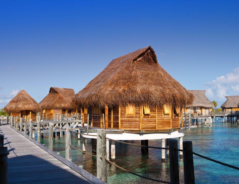 Camere con i tetti della paglia sopra il mare ad una luce solare calda fotografie stock