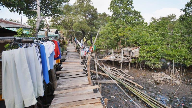 Camere del povero nei bassifondi filippini La palude Ponti di legno dalle plance su alta marea Vestiti sui pizzi immagine stock