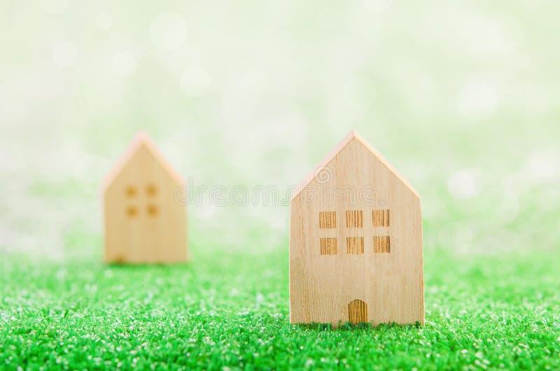 Camere di legno miniatura sul campo verde fotografie stock