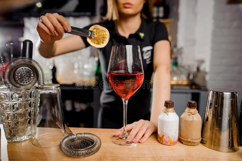 Cameriera al banco che aggiunge alla fetta del cocktail di limone facendo uso delle tenaglie immagine stock libera da diritti