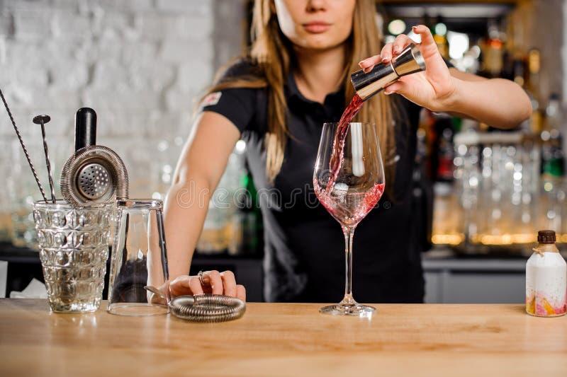 Cameriera al banco che prepara i cocktail in una barra per i suoi clienti immagini stock
