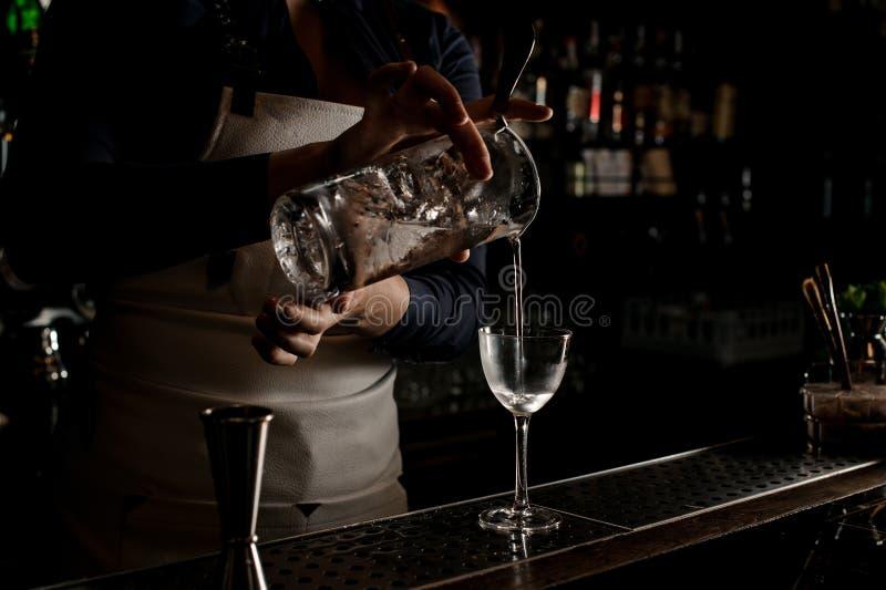 Cameriera al banco che versa cocktail fresco in un vetro immagini stock libere da diritti