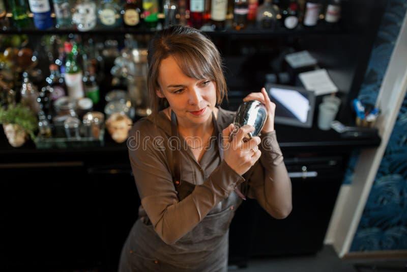 Cameriera al banco con l'agitatore che prepara cocktail alla barra immagini stock libere da diritti