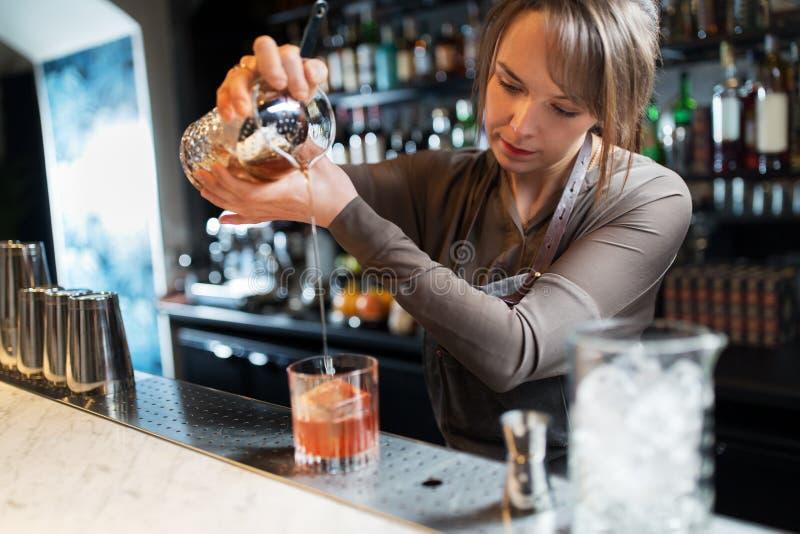 Cameriera al banco con vetro e la brocca che preparano cocktail fotografia stock