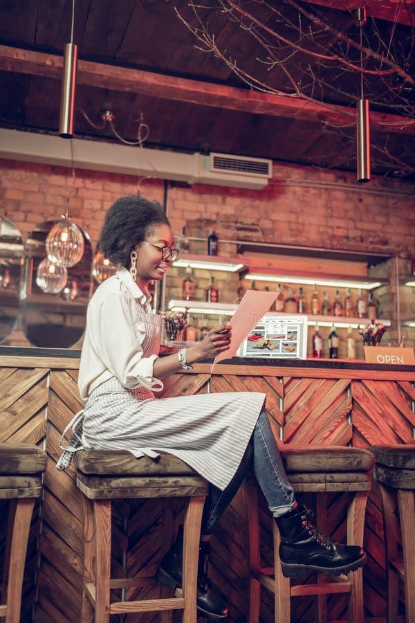 Cameriera al banco di fascino che controlla menu mentre avendo sedile alla sedia della barra fotografia stock