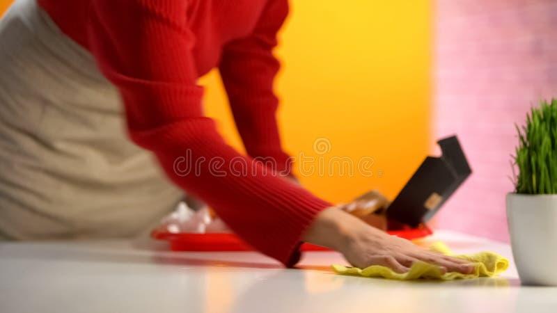 Cameriera di bar che pulisce tavola dopo i clienti in fast food, lavoro part-time immagini stock
