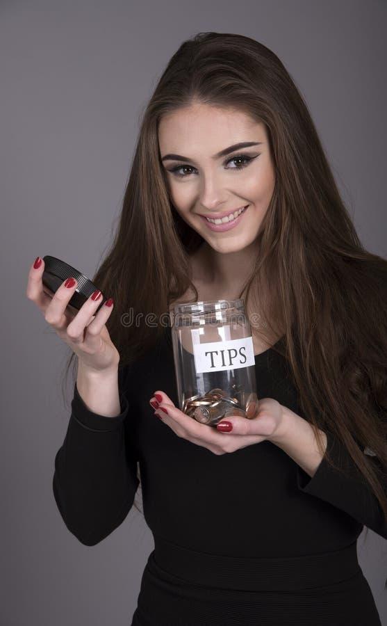 Cameriera di bar che tiene un contenitore ed i contanti di punte immagini stock