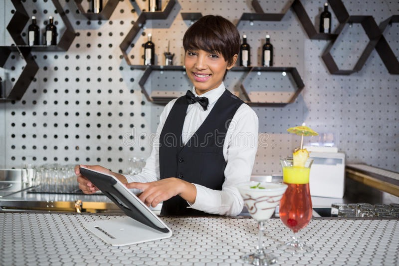 Cameriera di bar che utilizza compressa digitale nel contatore della barra fotografie stock libere da diritti