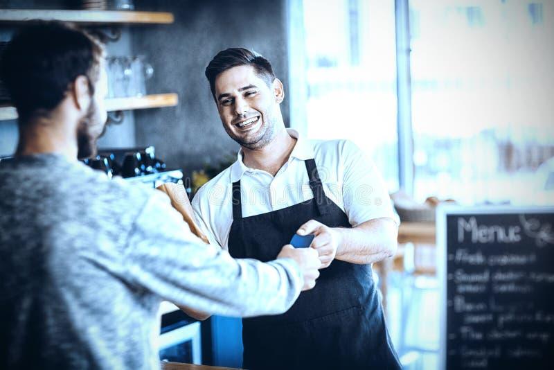 Cameriere che dà pane al cliente al contatore fotografia stock libera da diritti