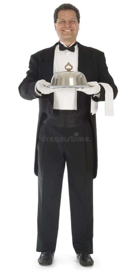 Cameriere che si leva in piedi sul bianco fotografia stock