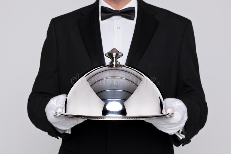 Cameriere che tiene un cloche d'argento fotografia stock