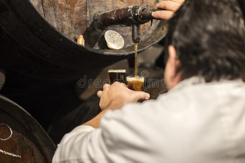 Cameriere che versa il vino dolce di Malaga dal barilotto fotografia stock