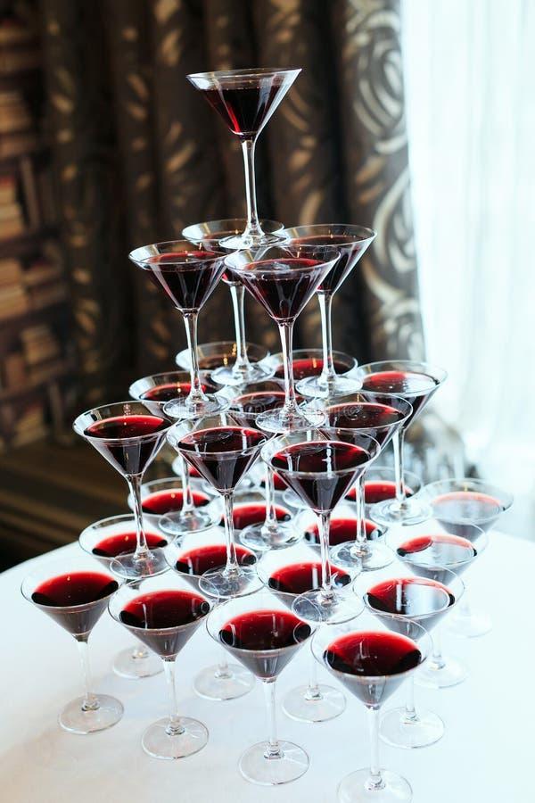 Cameriere che versa vino rosso o champagne nei vetri per il partito fotografia stock