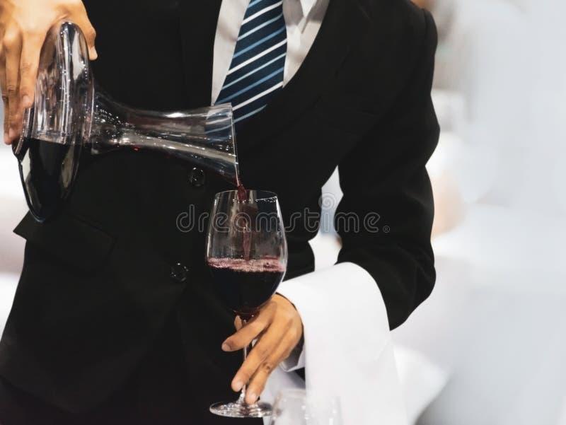 Cameriere che versa vino rosso in un vetro ad una tavola del ristorante immagine stock libera da diritti