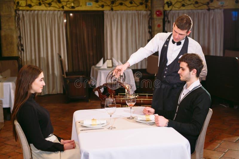 Cameriere che versa vino rosso in un vetro ad una tavola del ristorante fotografia stock