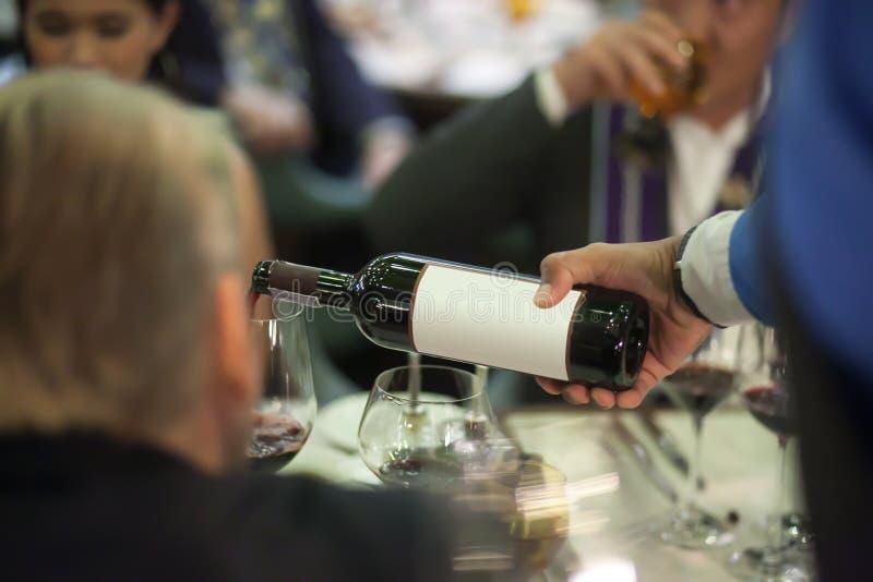 Cameriere che versa vino rosso in vetro di vino sulla tavola per servizio immagine stock libera da diritti