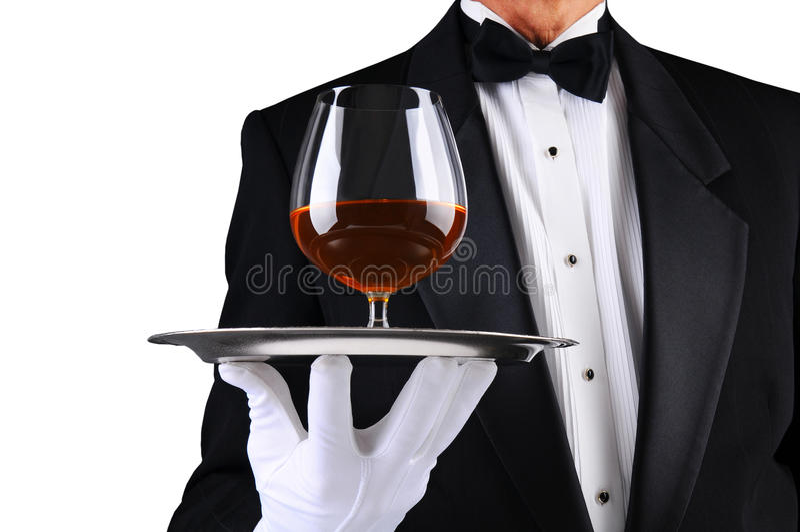 Cameriere con il bicchiere da brandy di brandy sul cassetto fotografia stock