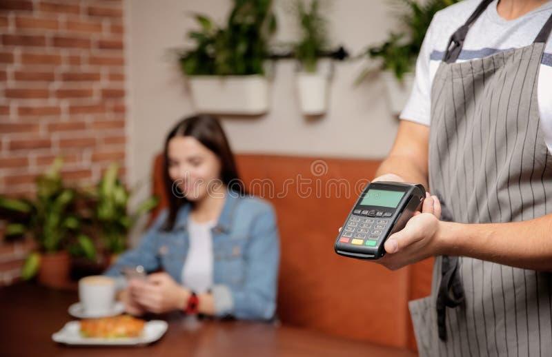 Cameriere con il terminale di pagamento in caffè, primo piano fotografia stock libera da diritti