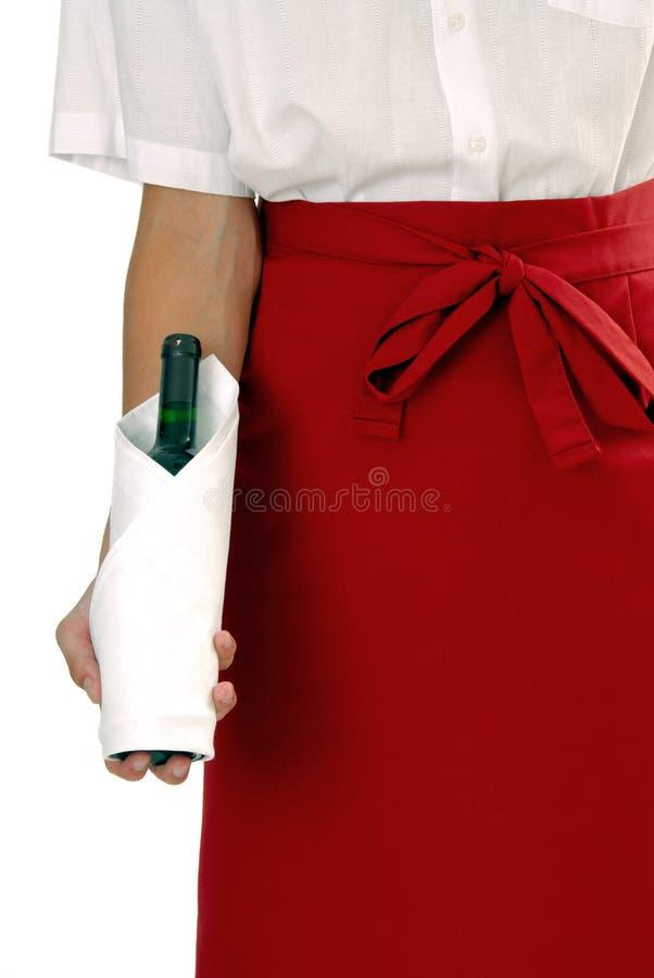 Cameriere in grembiule rosso con vino fotografia stock
