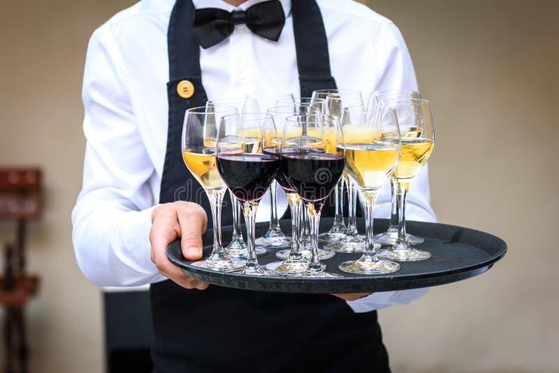 Cameriere professionista in uniforme del nero che serve vino rosso e bianco immagini stock libere da diritti