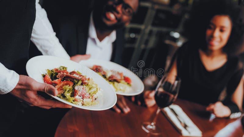 Cameriere Serving Salad al ristorante africano delle coppie immagini stock libere da diritti