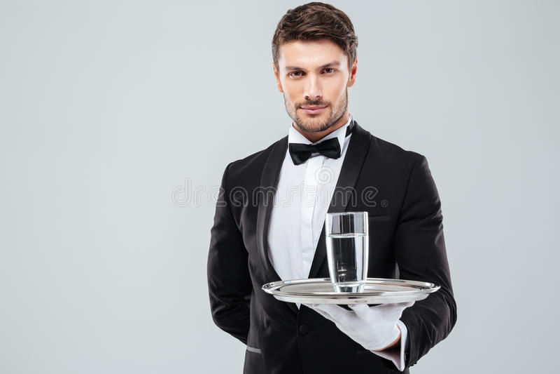 Cameriere in smoking che tiene bicchiere d'acqua sul vassoio del metallo fotografia stock libera da diritti