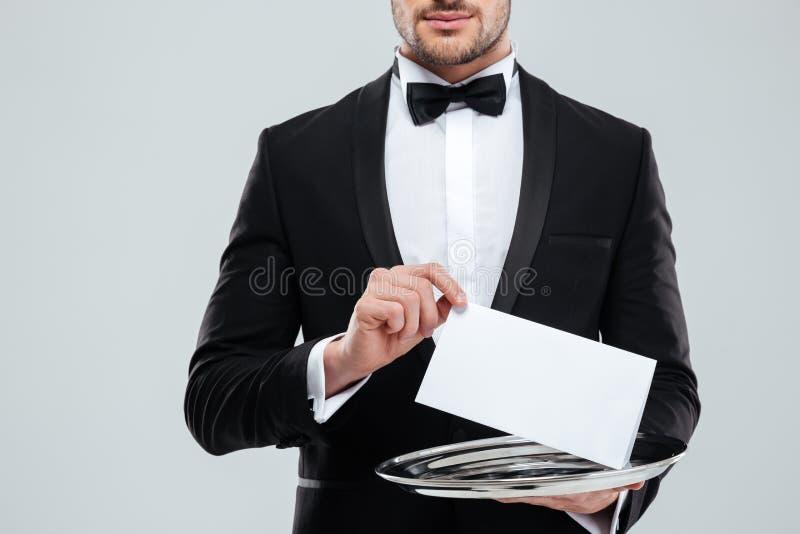 Cameriere in smoking con la cravatta a farfalla che tiene carta in bianco sul vassoio fotografia stock
