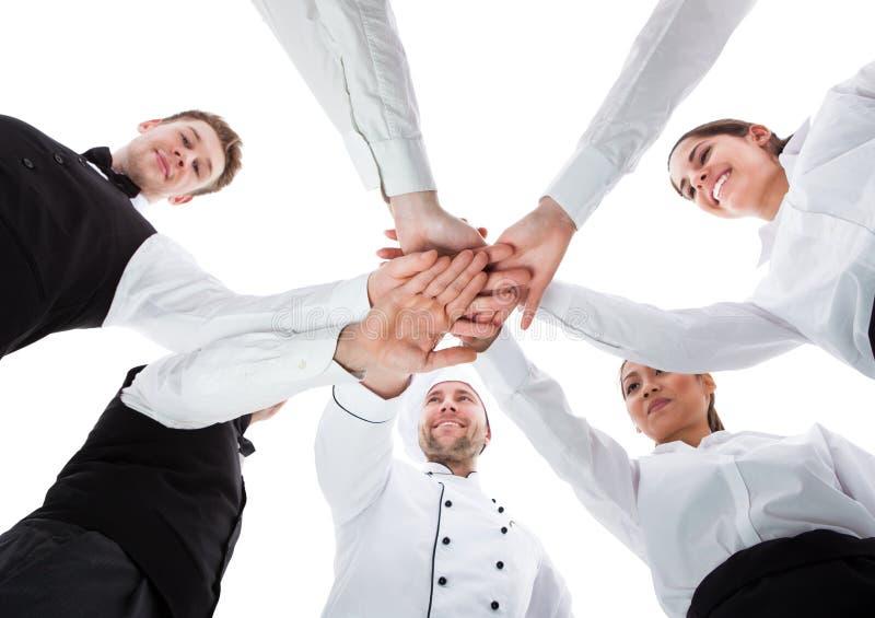 Camerieri e cameriere di bar che impilano le mani fotografia stock libera da diritti