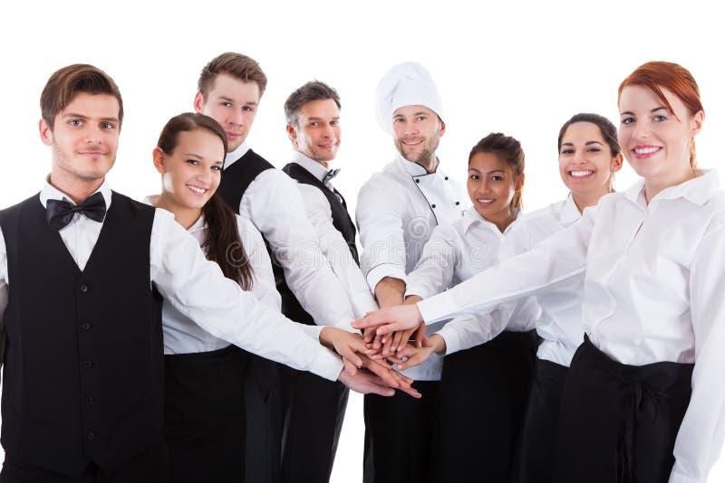 Camerieri e cameriere di bar che impilano le mani fotografie stock