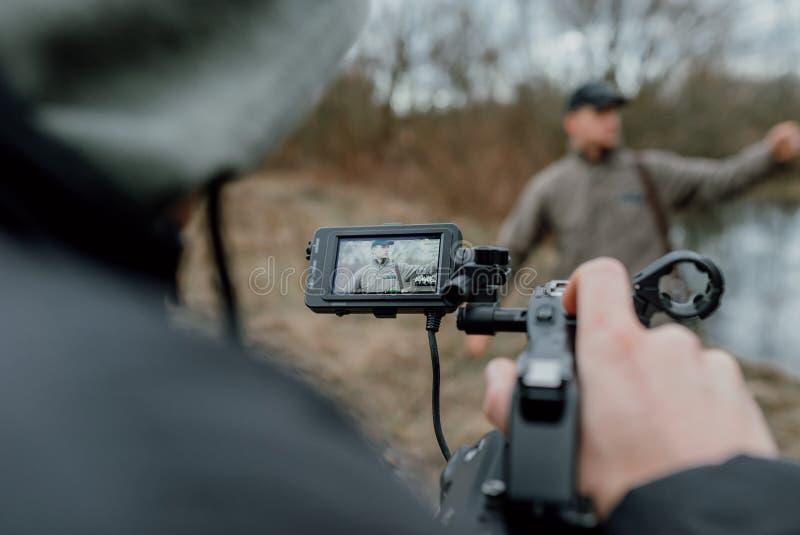 Camerman houdt camera en het registreren stock fotografie