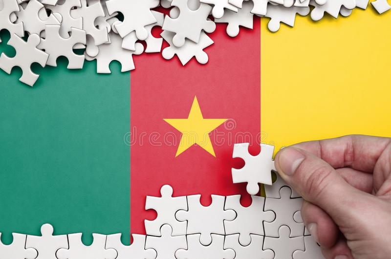 Cameroon flag is depicted on a table on which the human hand folds a puzzle of white color royalty free stock images