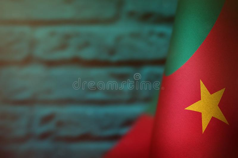 Cameroon flag for honour of veterans day or memorial day. Glory to the Cameroon heroes of war concept on light blue blurred. Cameroon hanging flag for honour of royalty free stock photos