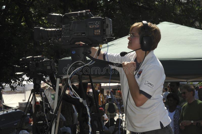 Camerwoman della TV che lega una manifestazione con un nastro fotografia stock libera da diritti