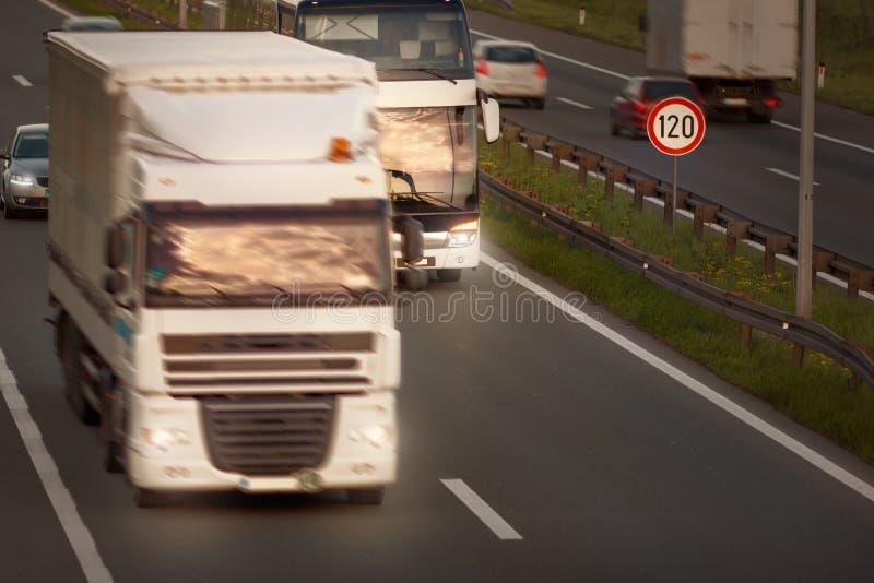 Camión blanco en la falta de definición de movimiento y autobús en la carretera fotografía de archivo