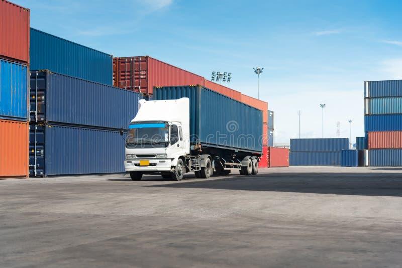 Camión con el contenedor para mercancías en el camino en yarda de envío fotografía de archivo libre de regalías