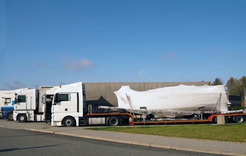 Camión con un remolque especial para el transporte del barco Transporte por tierra de barcos y de yates imagen de archivo