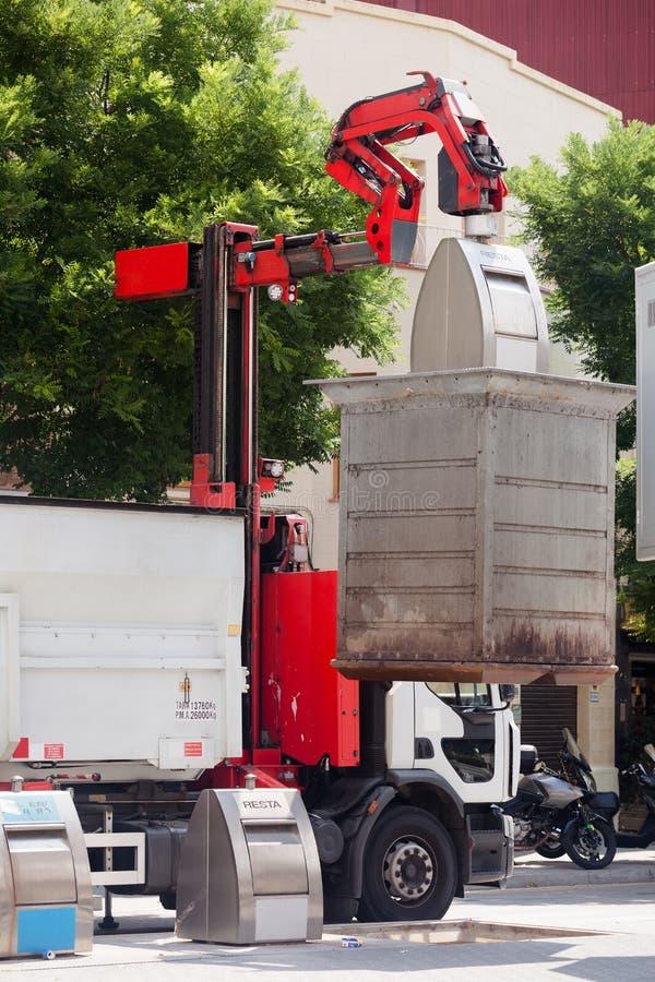 Camión de basura que recoge los cubos de la basura fotos de archivo