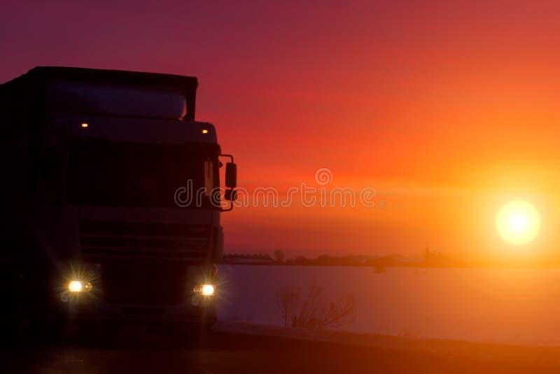 Camión de la silueta con el envase en la carretera, concepto del transporte del cargo Fondo de la puesta del sol con el espacio d imágenes de archivo libres de regalías