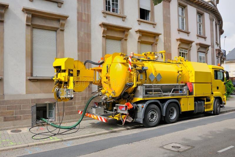 Camión de las aguas residuales que trabaja en el ambiente urbano de la ciudad imágenes de archivo libres de regalías
