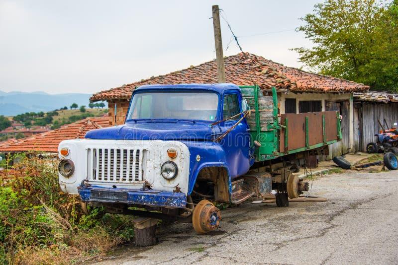 Camión de remolque en hierba delante del montañas foto de archivo libre de regalías