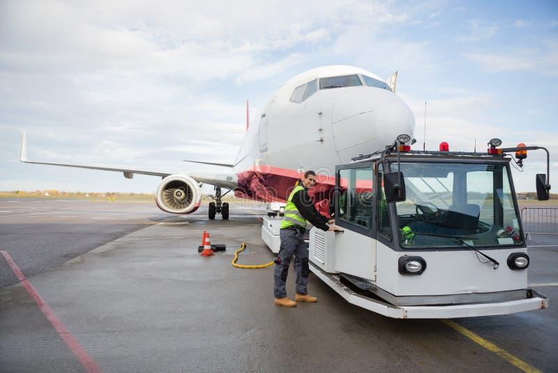 Camión de remolque de la abertura del trabajador atado al aeroplano imágenes de archivo libres de regalías