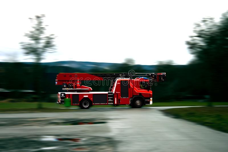 Camión del bombero que conduce rápidamente en un camino mojado imágenes de archivo libres de regalías