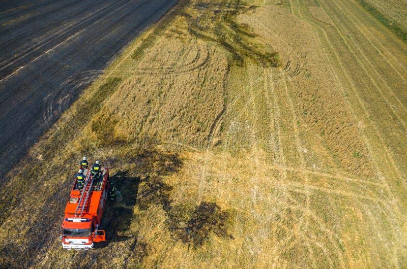 Camión del bombero que trabaja en el campo en el fuego imagen de archivo libre de regalías
