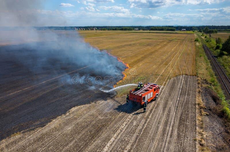Camión del bombero que trabaja en el campo en el fuego foto de archivo libre de regalías