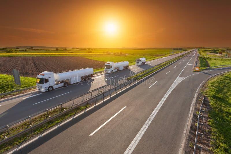 Camión del depósito de gasolina en la falta de definición de movimiento en la carretera en la puesta del sol imagen de archivo