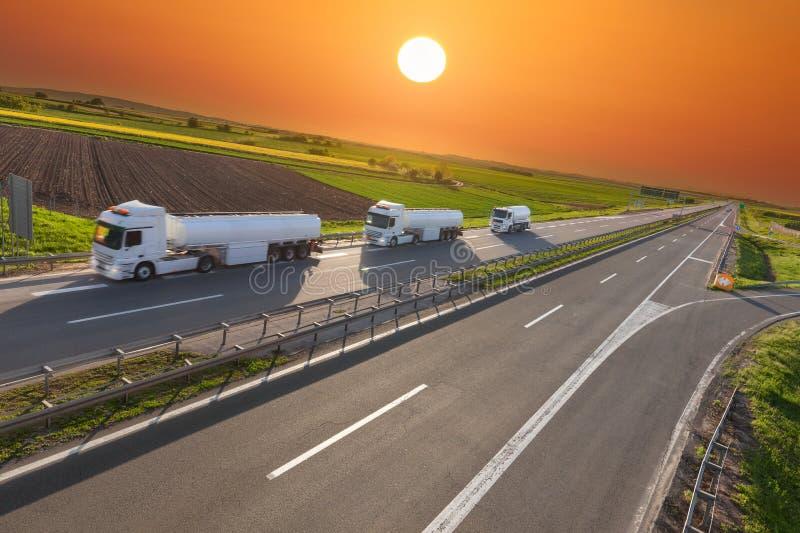 Camión del depósito de gasolina en la falta de definición de movimiento en la carretera en la puesta del sol fotografía de archivo libre de regalías