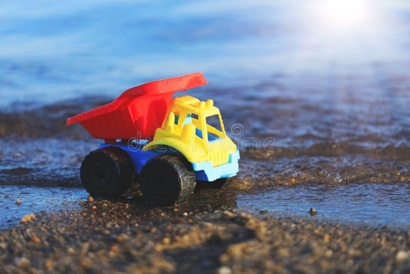 Camión del juguete en la playa arenosa del oro Coche rojo, azul y amarillo en t imagenes de archivo