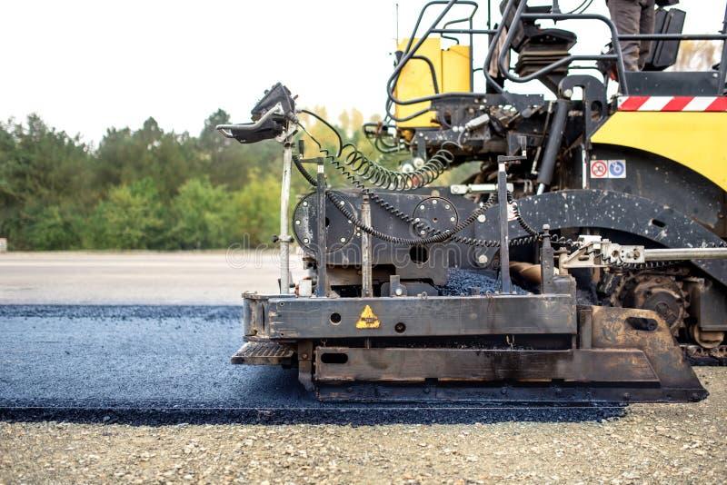 Camión del pavimento que pone el asfalto fresco en el emplazamiento de la obra, asfaltando imagen de archivo libre de regalías