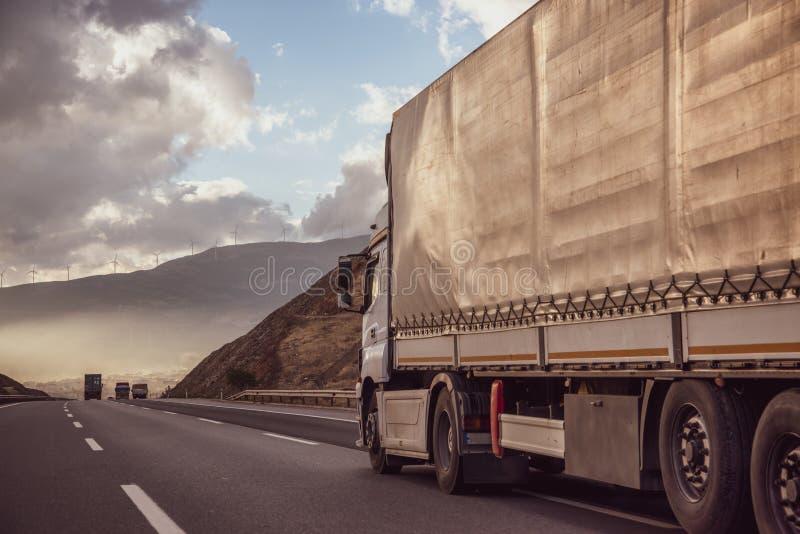 Camión en el camino en un paisaje rural en la puesta del sol Transporte de carga del transporte y del cargo de la logística imagen de archivo libre de regalías
