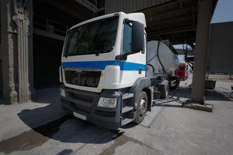 Camión en la descarga en un almacén Una pista para el transporte y el envío en un fondo de la fábrica Negocio industrial fotografía de archivo libre de regalías